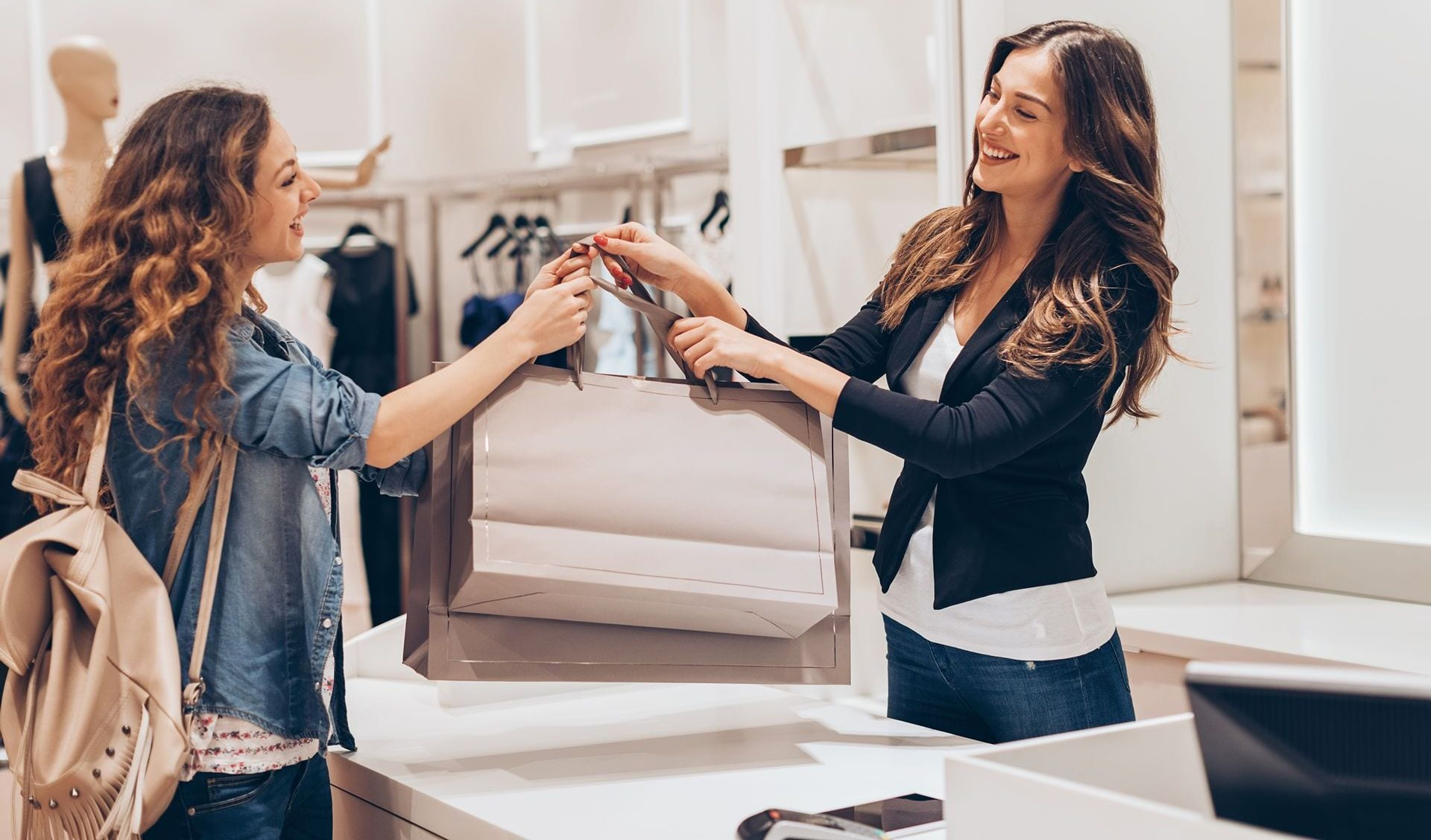 Young woman taking her shopping bags in a fashion store